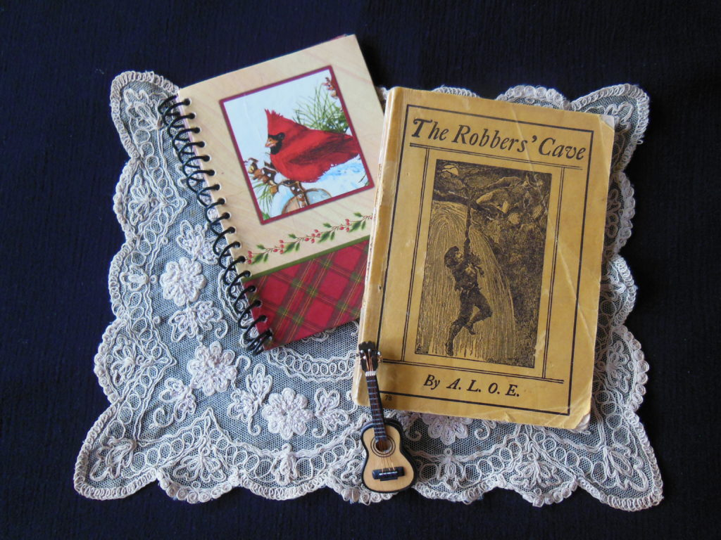 a book, a notebook, and a miniature guitar laying on a lace doily