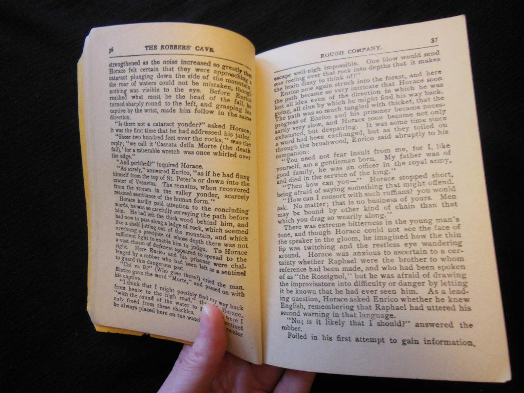 a hand holding an open book