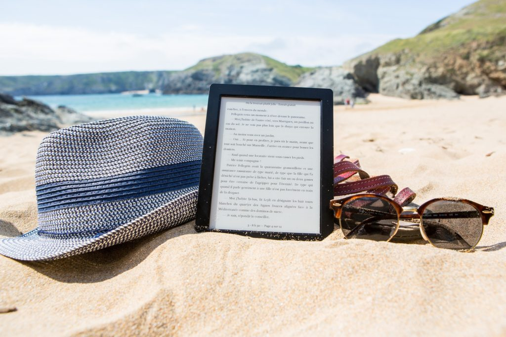 an e-reader on the beach with sandals, a sun hat, and sunglasses around it
