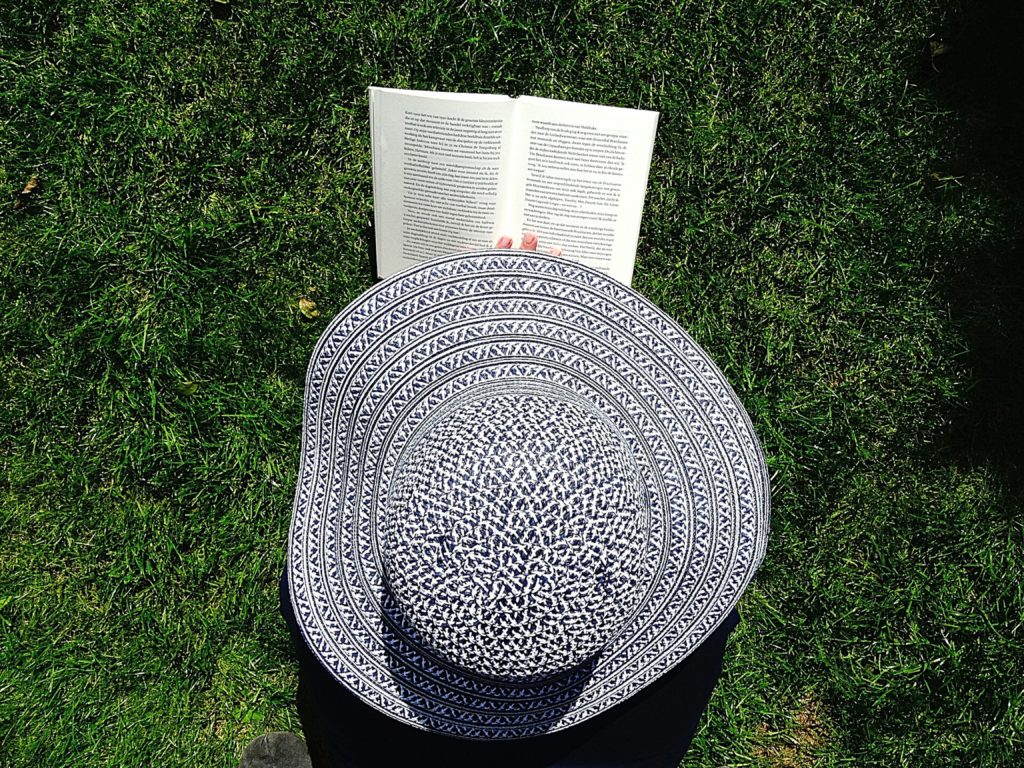 Hat and book on grass | good reading material