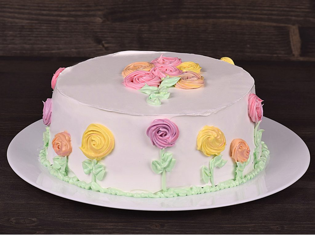 A cake with icing flowers and leaves on it