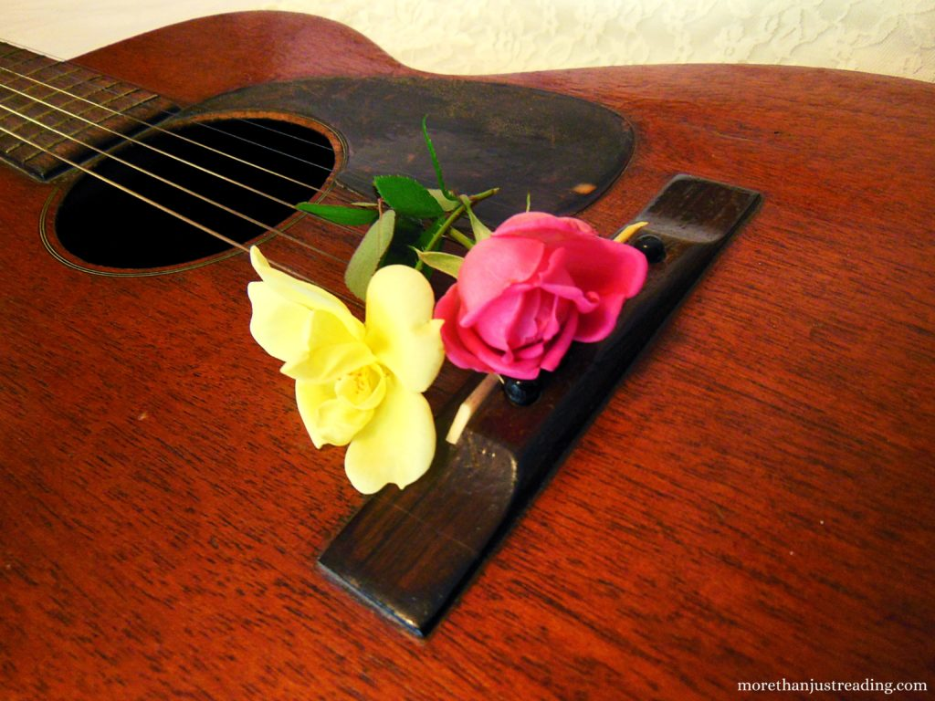 Roses resting on the head of a guitar