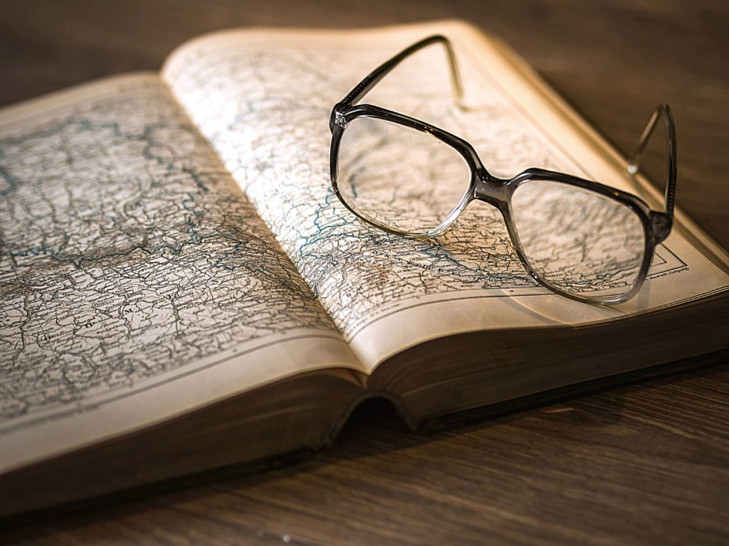 Glasses on open book of maps