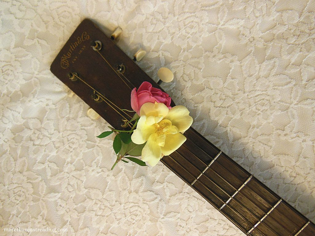 Roses resting on the neck of a guitar