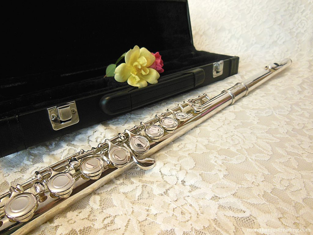 A flute next to a flute case with roses in it