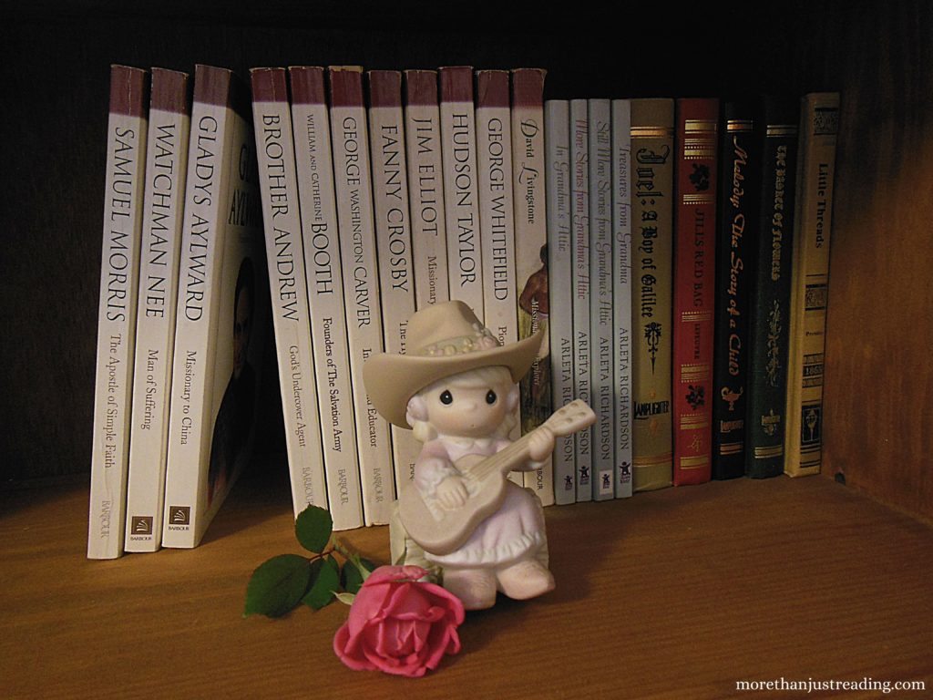 books on a shelf with a precious moments figurine and a pink rose in front of them