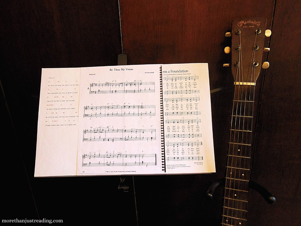A guitar on a stand next to a music stand with sheet music on it