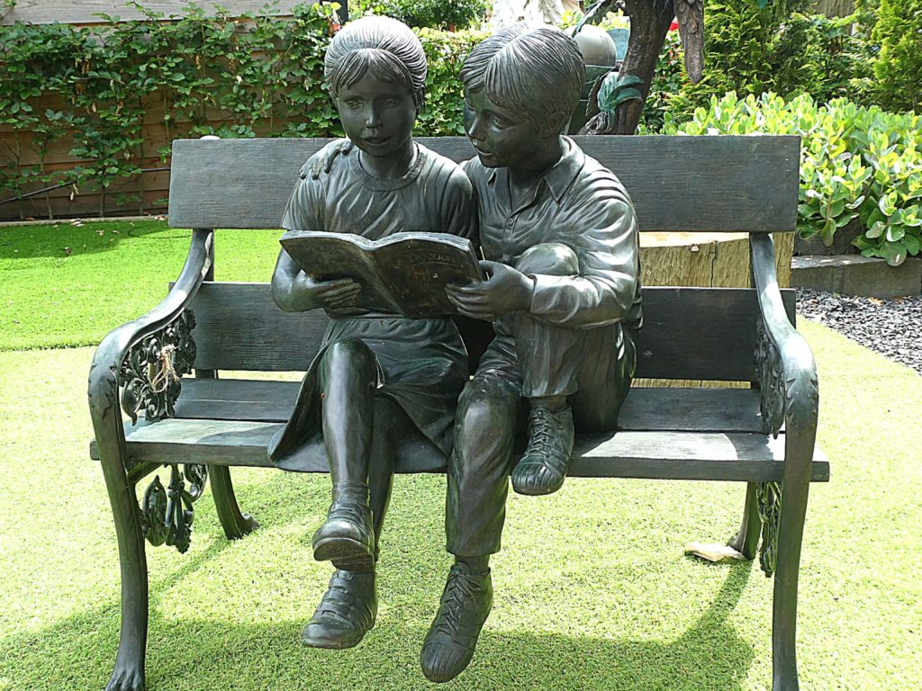 Statue of a boy and a girl sitting on a bench reading | Isabella Alden