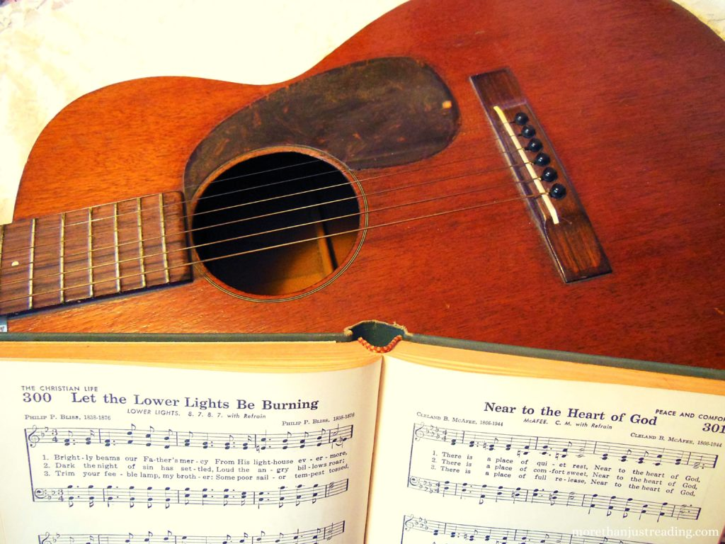 A hymn book leaning against the head of a guitar | practicing hymns